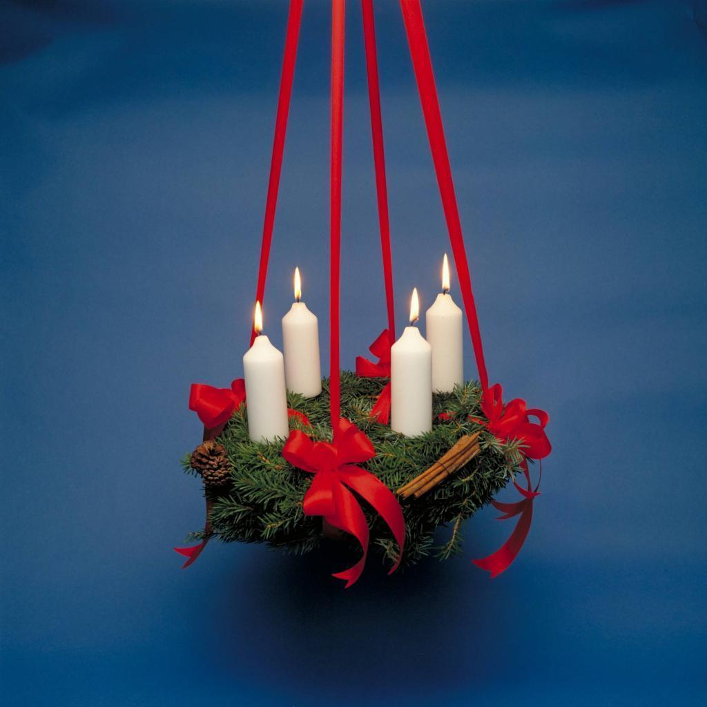Traditionally, an Advent Wreath in Denmark is made out of fine spruce twigs and cuttings. It is also often decorated with red berries and spruce cones. What is then added for decoration?